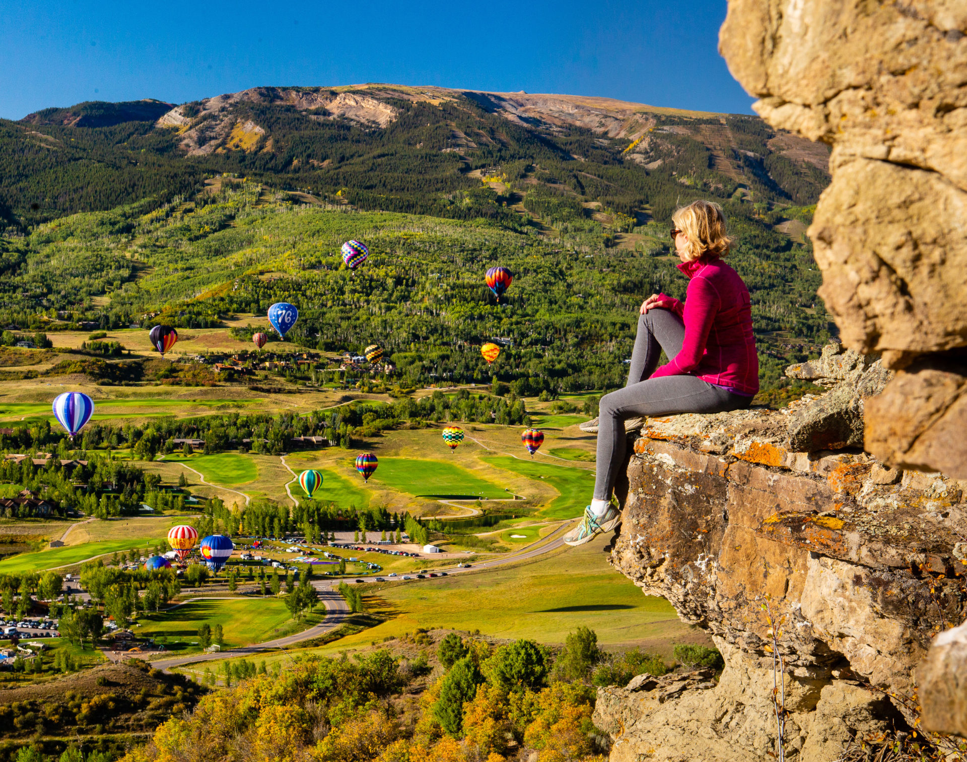 Woman watching hot air balloons from side of cliff