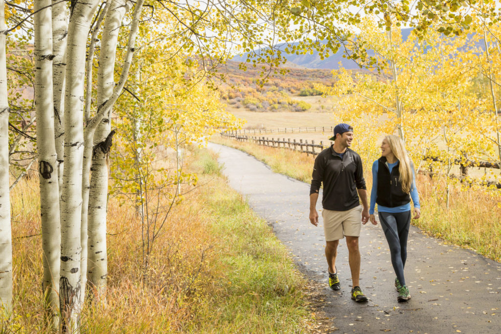 A couple walking a trail outside during fall